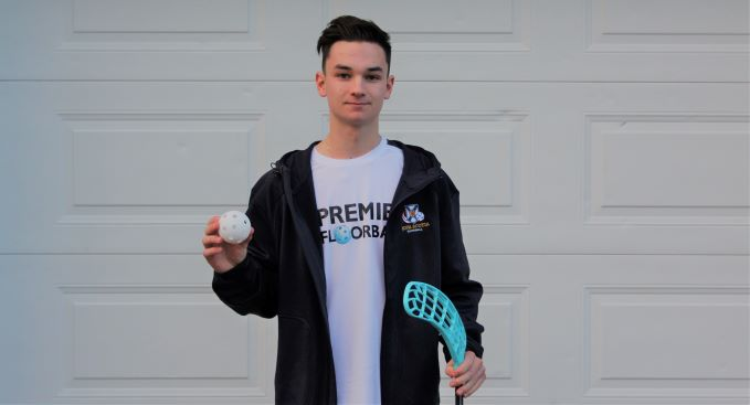 Ethan Morgan holding a floorball stick and ball at his home in Bedford.