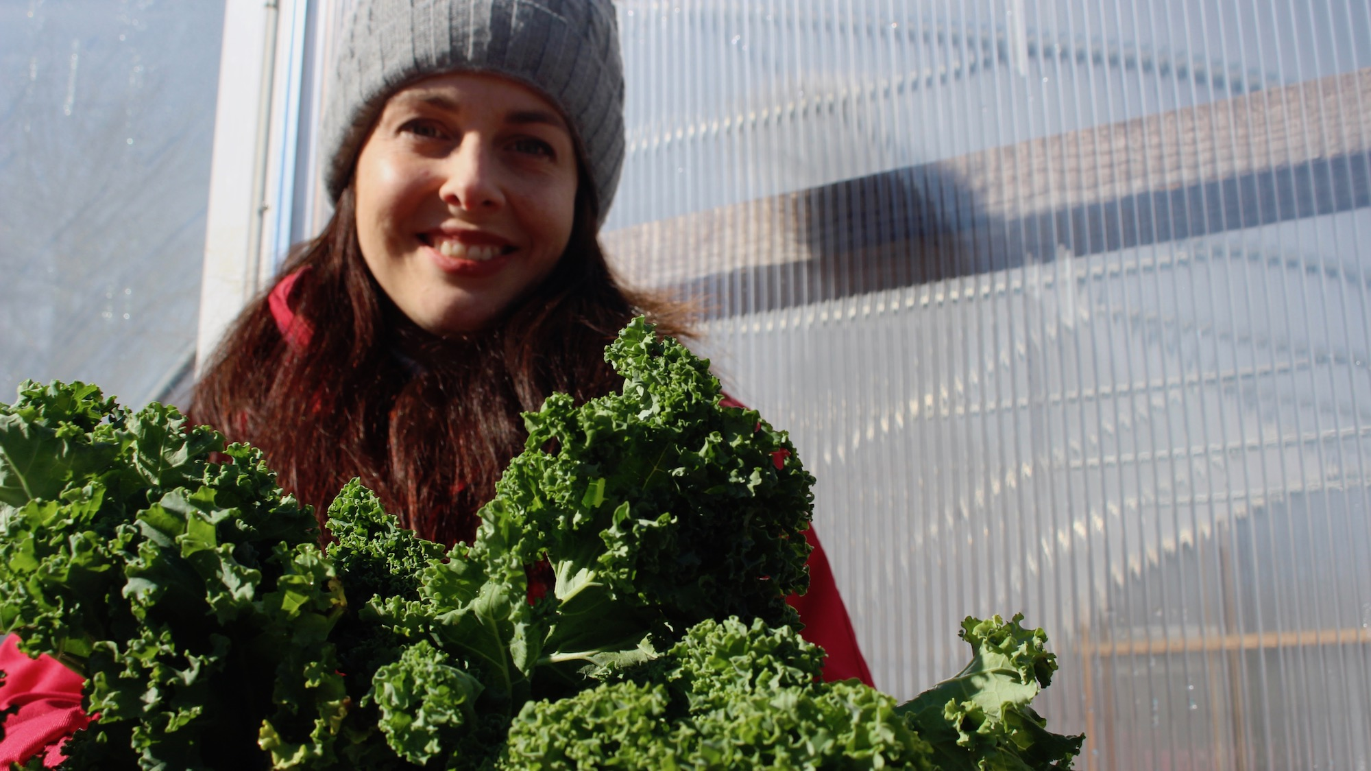 Niki Jabbour poses with kale outside her polytunnel.