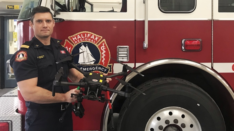 Captain Richard Sullivan stands in front of a Highfield Park fire truck holding the department's Matrice 210 drone.
