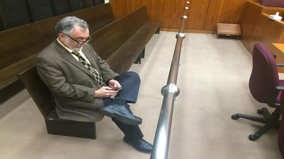 John Piccolo, the director of communications for the Nova Scotia Judiciary, reads from his Blackberry in an empty courtroom at the Halifax Law Courts.