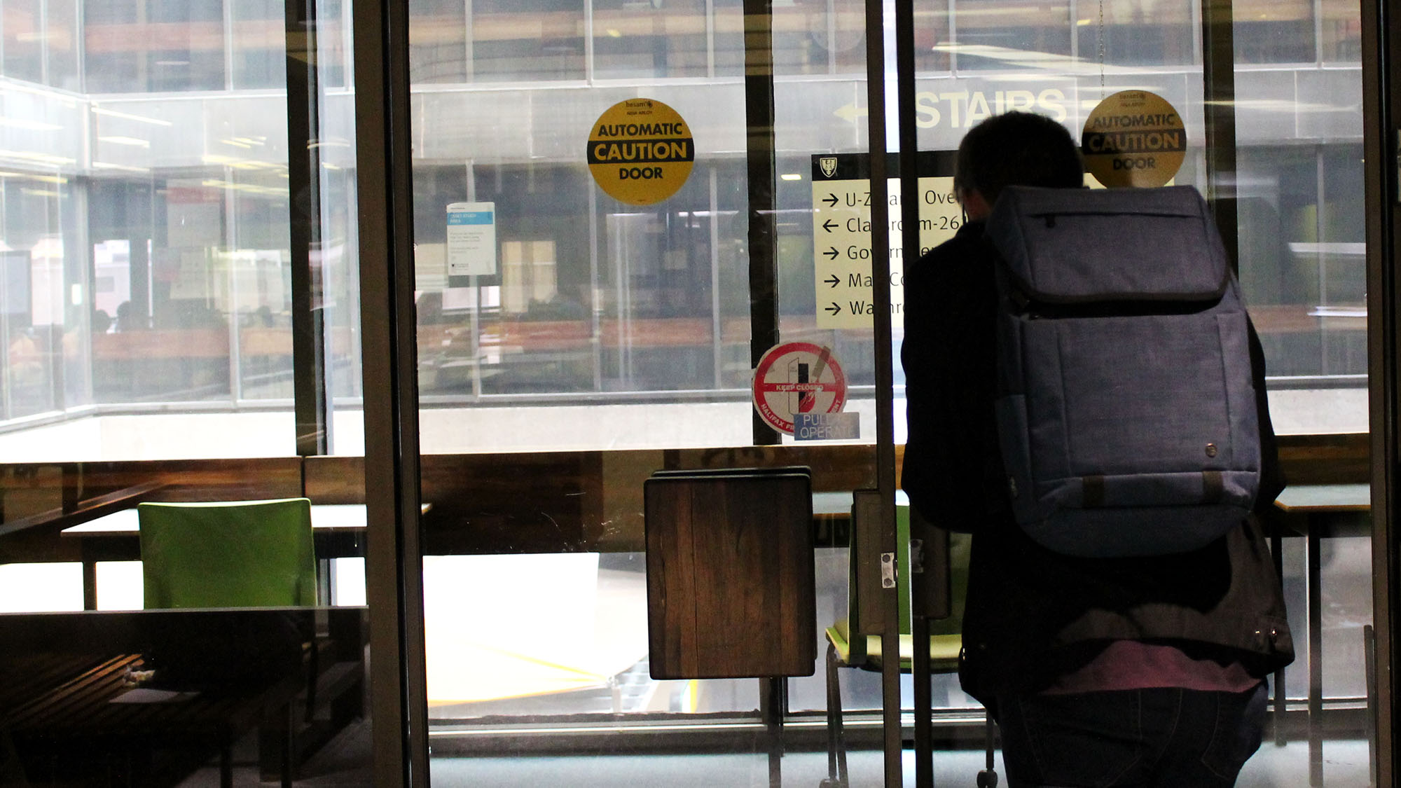 A Dalhousie student pushes through the doors at the Killam Library.