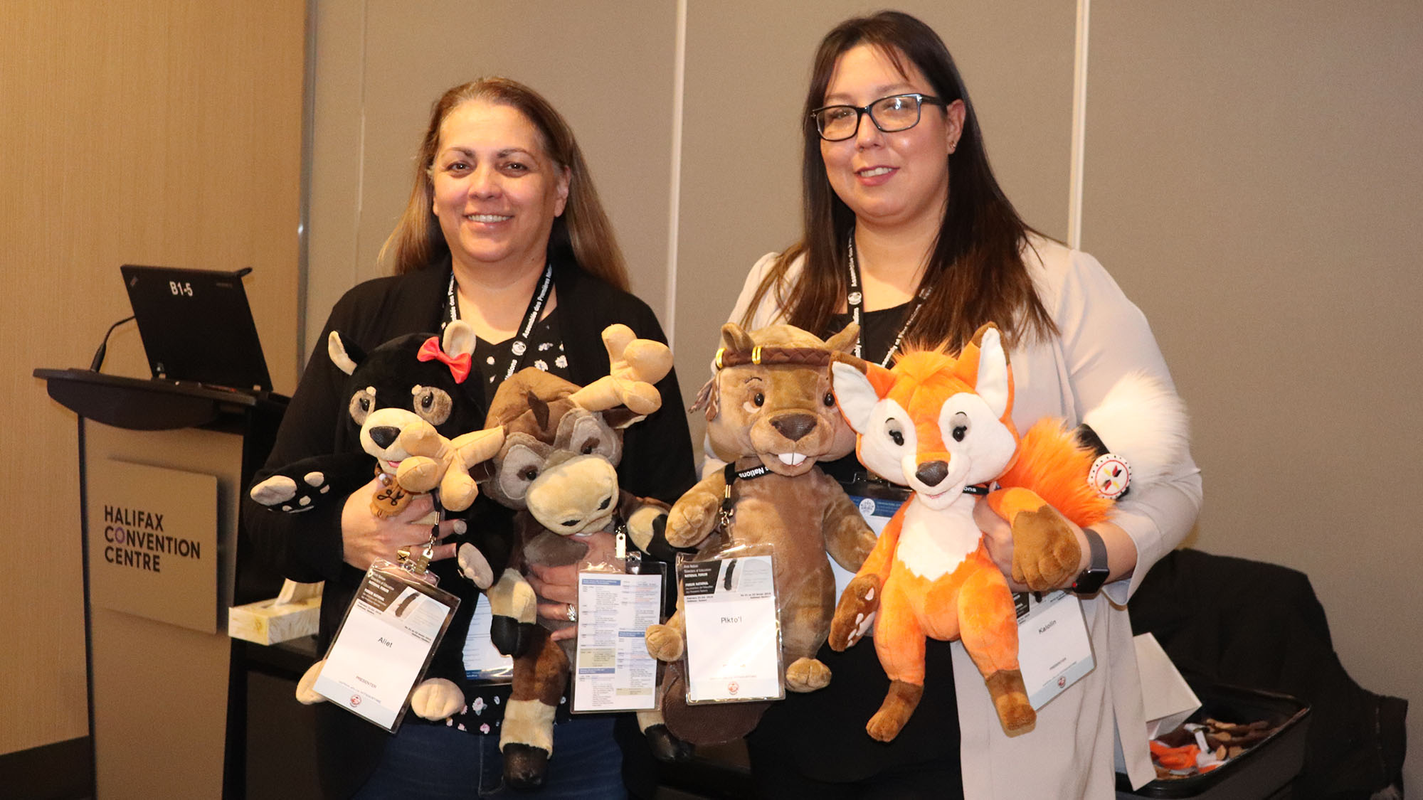 Yoland Denny (left) and Blaire Gould (right) hold up the four puppets Aliet, Antle, Pikto'l and Kalolin.