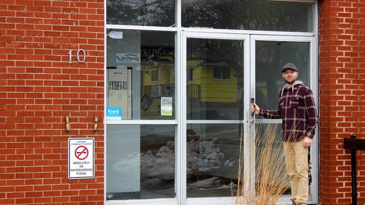 man stands next to building doors