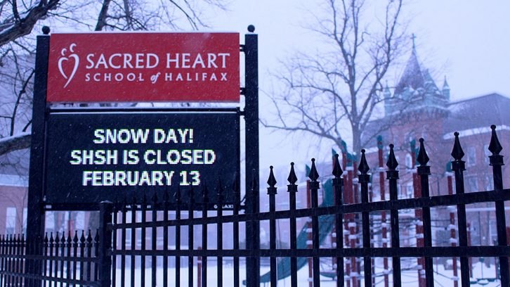 """Sign outside of school reads: """"Snow day!; SHSH closed; February 13"""""""