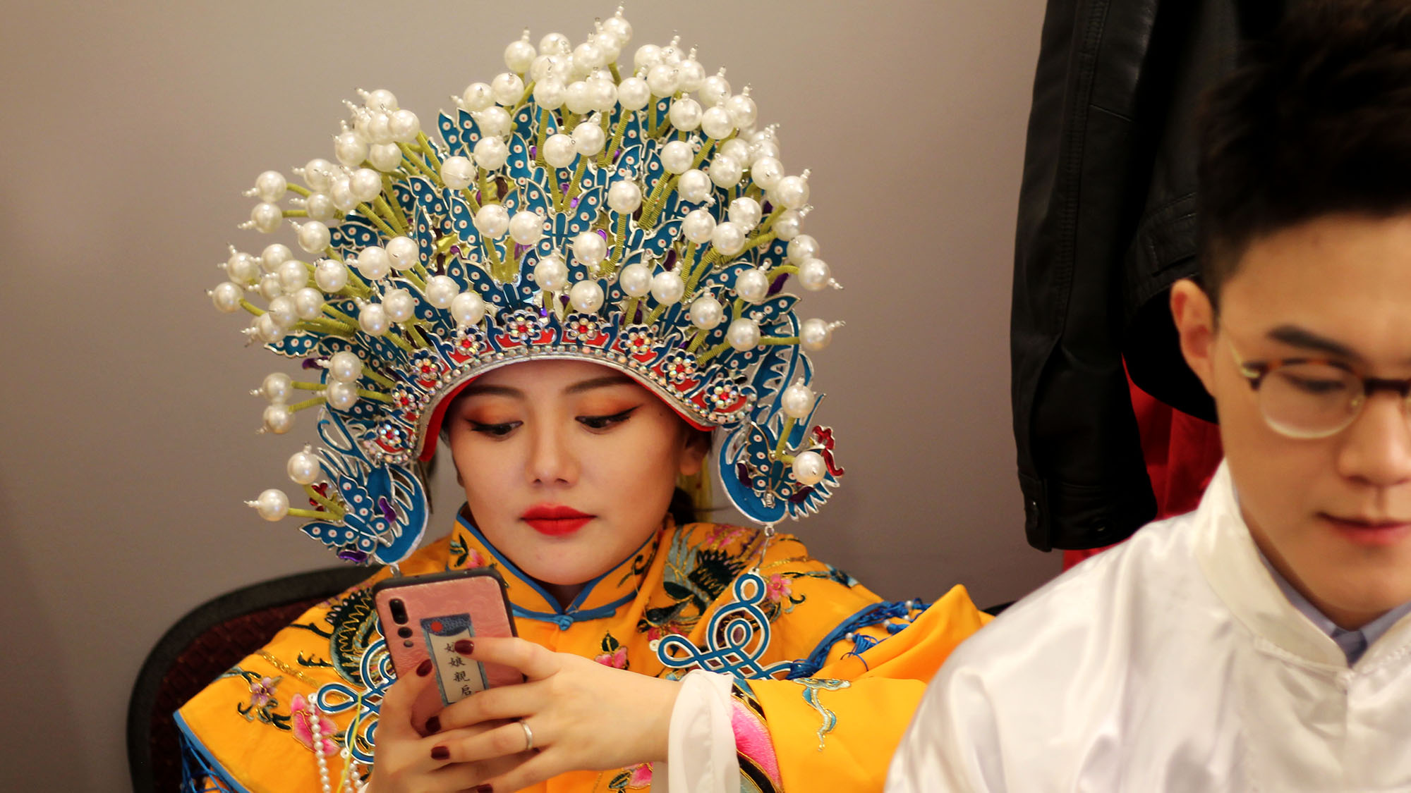 A woman checks her phone in a dressing room while waiting to perform at a gala on Feb. 2.