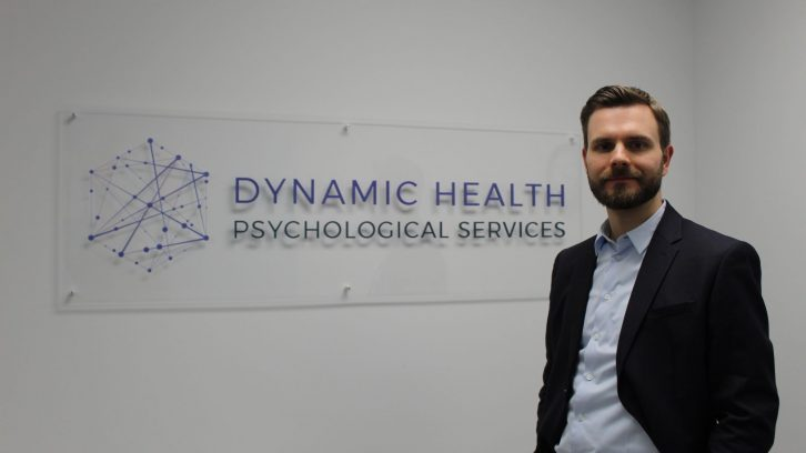 Dr. Joel Town stands in front of the sign for Dynamic Health Psychological Services
