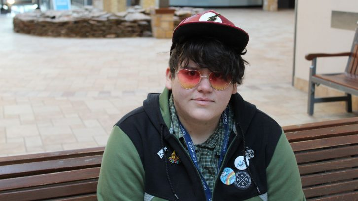 "Jace Miller sits on a bench wearing heart-shaped sunglasses and buttons on his sweater. One reads, ""I'm way over the rainbow."""