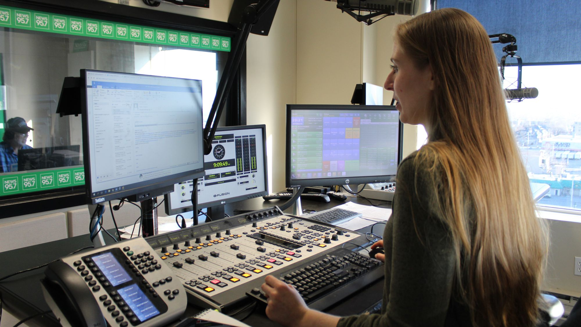 Katie Hartai stands at her desk in the radio room at News 95.7. In the background Rick Howe can be seen talking on the radio.