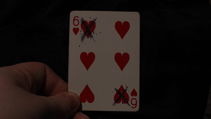 A six of hearts card with two of the hearts crossed out