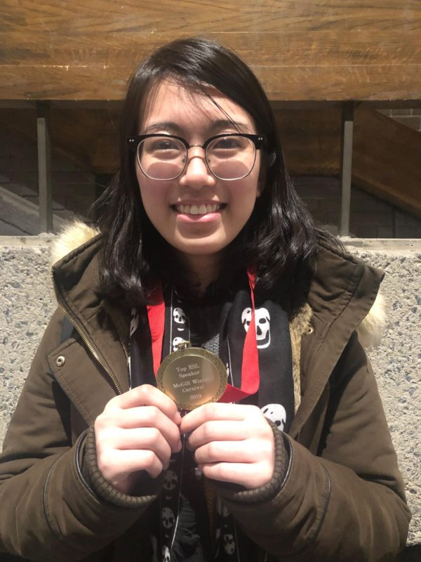 Yankun Li holding a medal she won at a McGill debate tournament