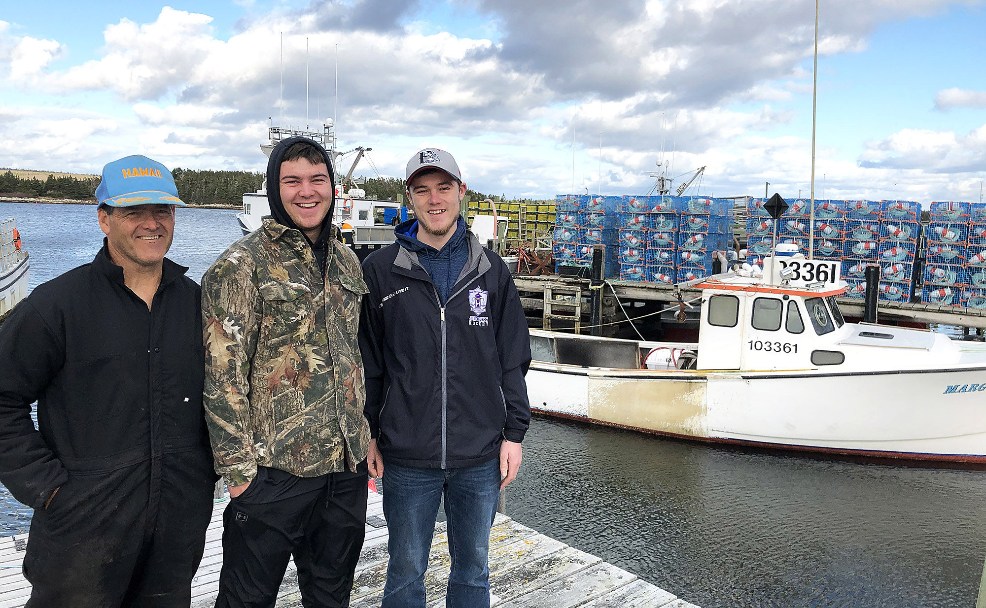 Kenny Henneberry stands with his sons Logan and Garrett in front of his brother's fishing boat at their family wharf in Sambro, N.S.