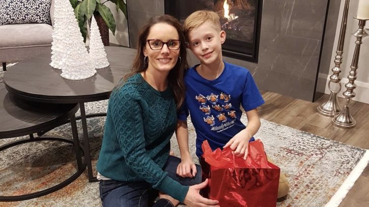"""Tammy Clarke and son Tanner. Clarke says collecting and wrapping purses is her """"little tradition to give back."""""""