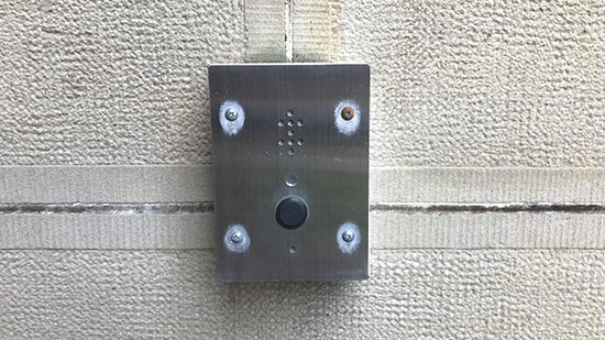 The unmarked buzzer near ramp entrance.