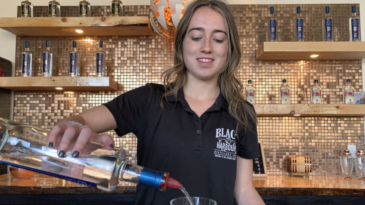 Jaime Landry pouring a drink at her bar in Fox Point, N.S.