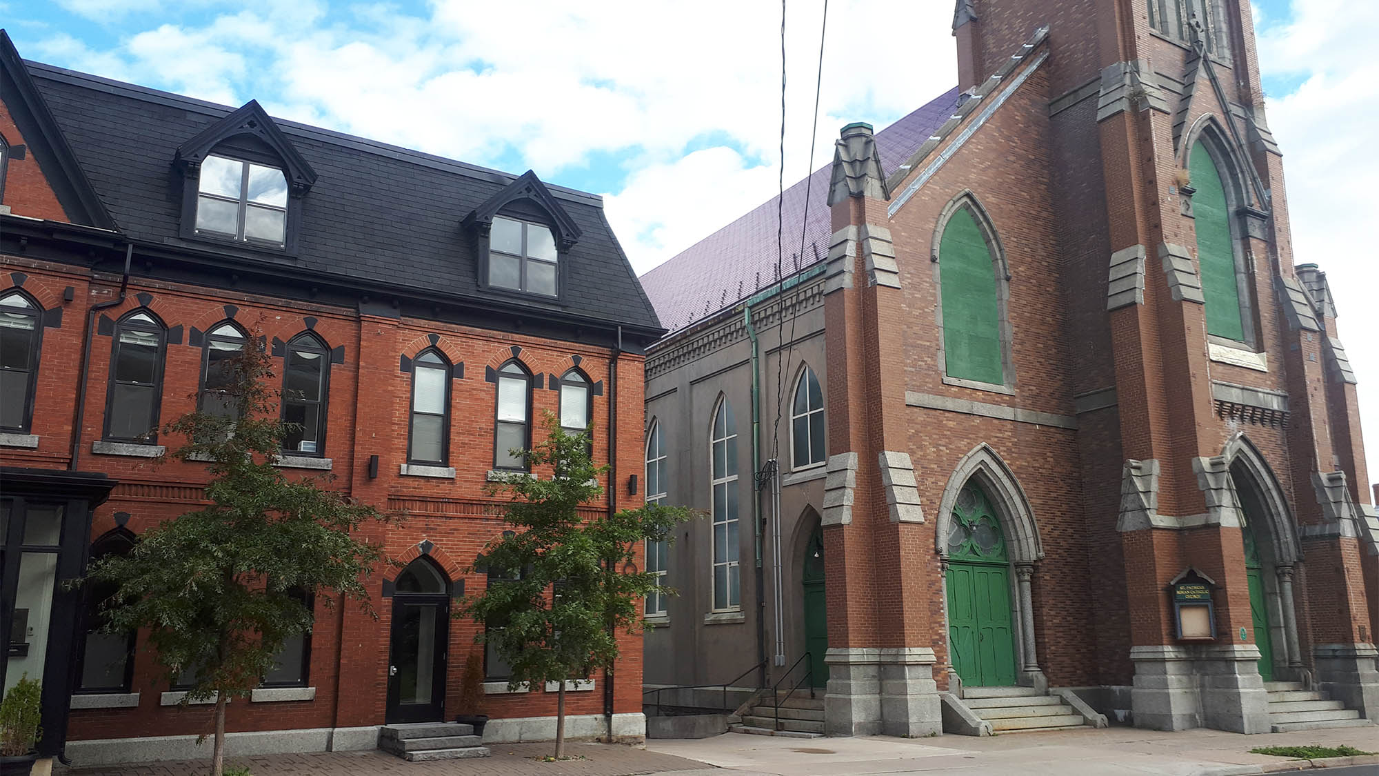 The approved building is to be constructed behind the old rectory (left), adjacent to St. Patrick's Church (right).