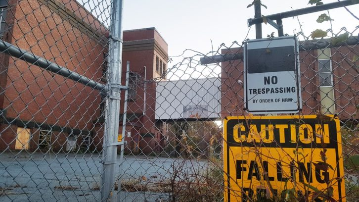 Bloomfield Centre's building, showing a bent fence and 'no trespassing' signs.