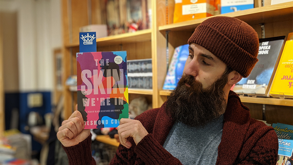 Paul MacKay, who manages the King's Co-op Bookstore, holds an advanced copy of Desmond Cole's The Skin We're In.