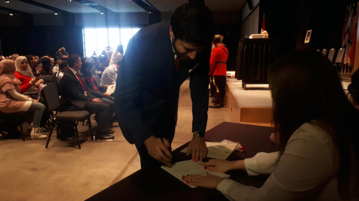 Peace by Chocolate CEO Tareq Hadhad signs his Canadian citizenship.
