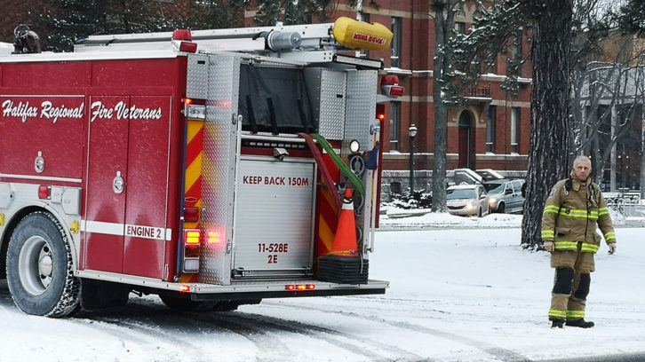 A firefighter standing next to a fire truck on University Avenue, Halifax.