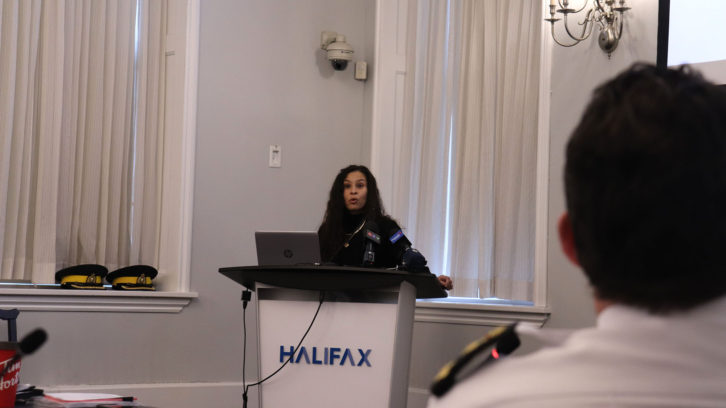 HRP Chief Dan Kinsella (foreground) watches Halifax activist El Jones speak at the board of police commissioners meeting on Monday. Jones said the police budget should be frozen until HRP takes better action on racial profiling.