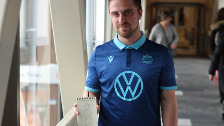 James Janssen poses with his sketchbook, where he's sketched some of the fans of the Wanderers.