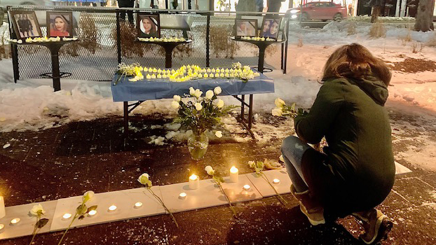 A woman attending Wednesday night's vigil places a white rose at the foot of the memorial.