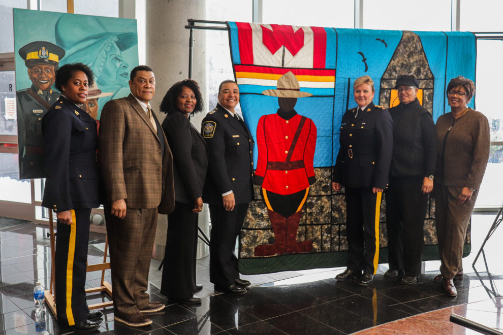 "Attendees at the Feb. 13 RCMP event for ""Her Story"" pose with a painting and quilt made to commemorate black canadians in law enforcement."
