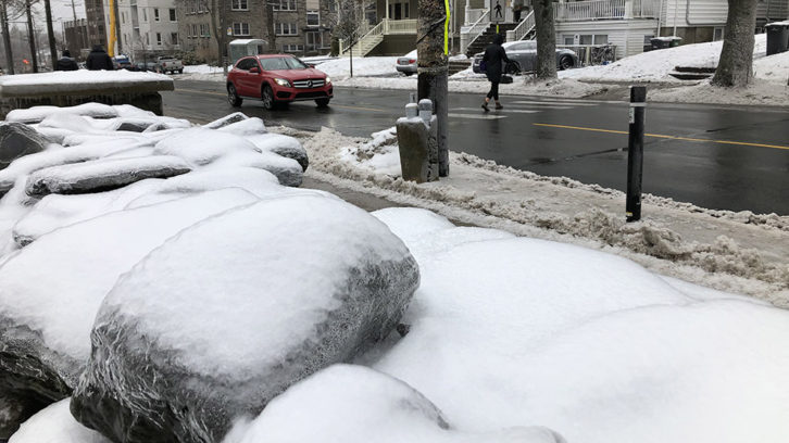 Ice covers rocks alongside Coburg Road at noon on Friday.