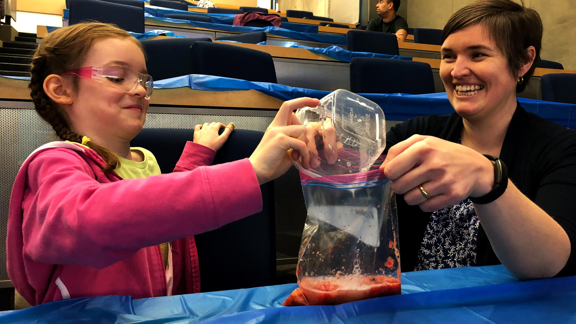Eleanor Redmond pours her mixture into some smashed strawberries with help from her mom, Jessica.