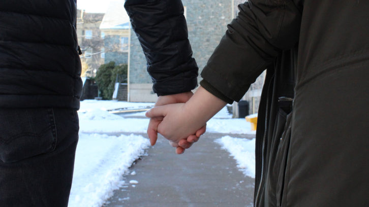 Photo illustration of two people holding hands