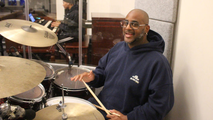 Floyd Colley sits at his drum set for a church band practice.