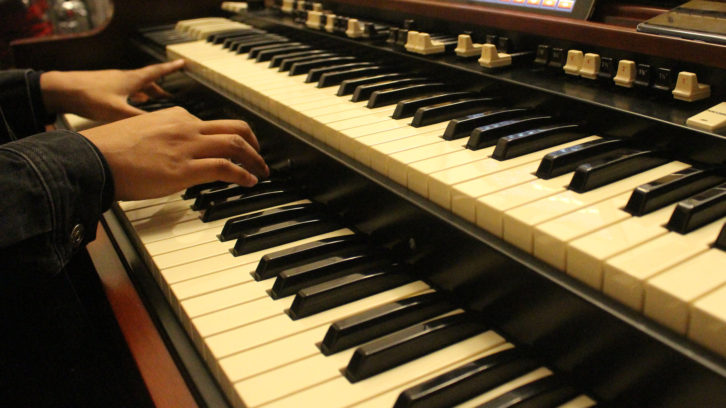 A close-up of Reeny Smith playing the organ in church.