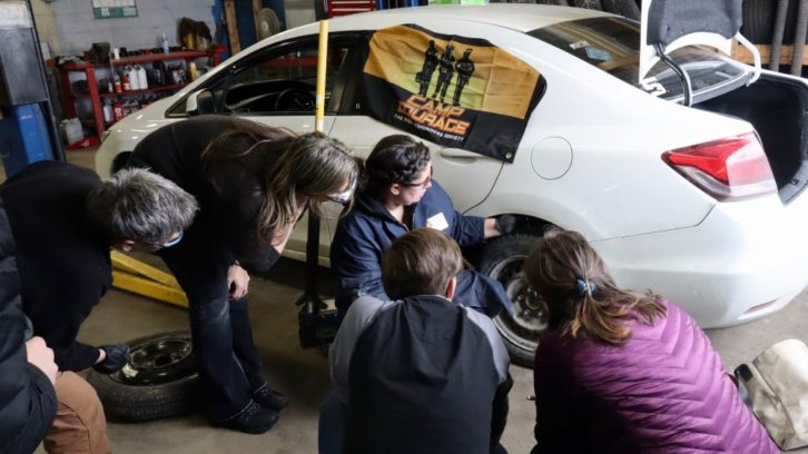 Robin Croft shows automotive workshop participants how to check tire pressure at Coast Tire and Auto Service in Dartmouth on March 8. The workshop was run by Camp Courage.