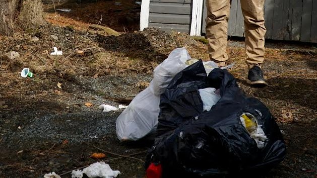 Keigan Davis stands near trash that was illegally dumped on his property in Halifax.
