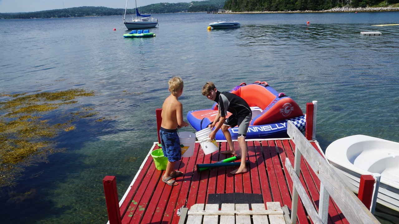Two kids playing on a dock