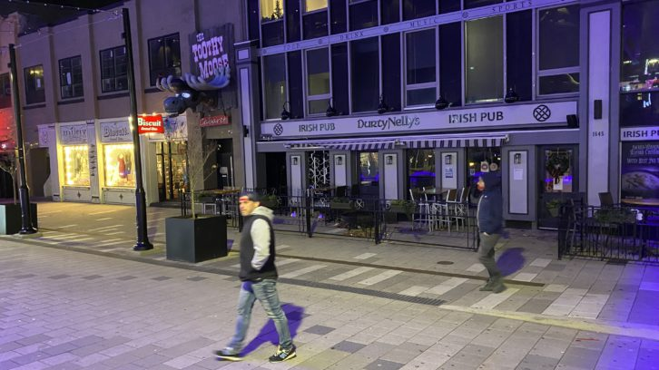 Pedestrians cross in front of a closed Durty Nelly's Irish Pub in Halifax's deserted entertainment district Tuesday night.