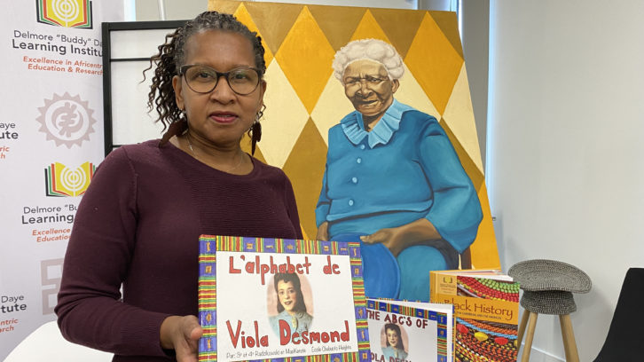 "Sylvia Parris-Drummond poses with a selection of the Delmore ""Buddy"" Daye Learning Institute's educational materials and a painting by local artist Letitia Fraser that will be featured on the cover of a forthcoming textbook."