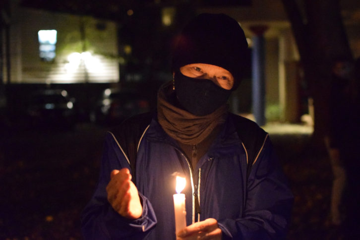 A woman wearing a winter coat, a mask, and a toque holds a lit candle in a park.