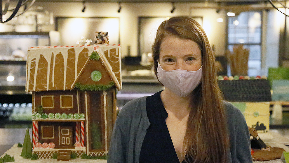 Katie MacLeod poses in front of her gingerbread house at The Old Apothecary Bakery and Café on Monday.