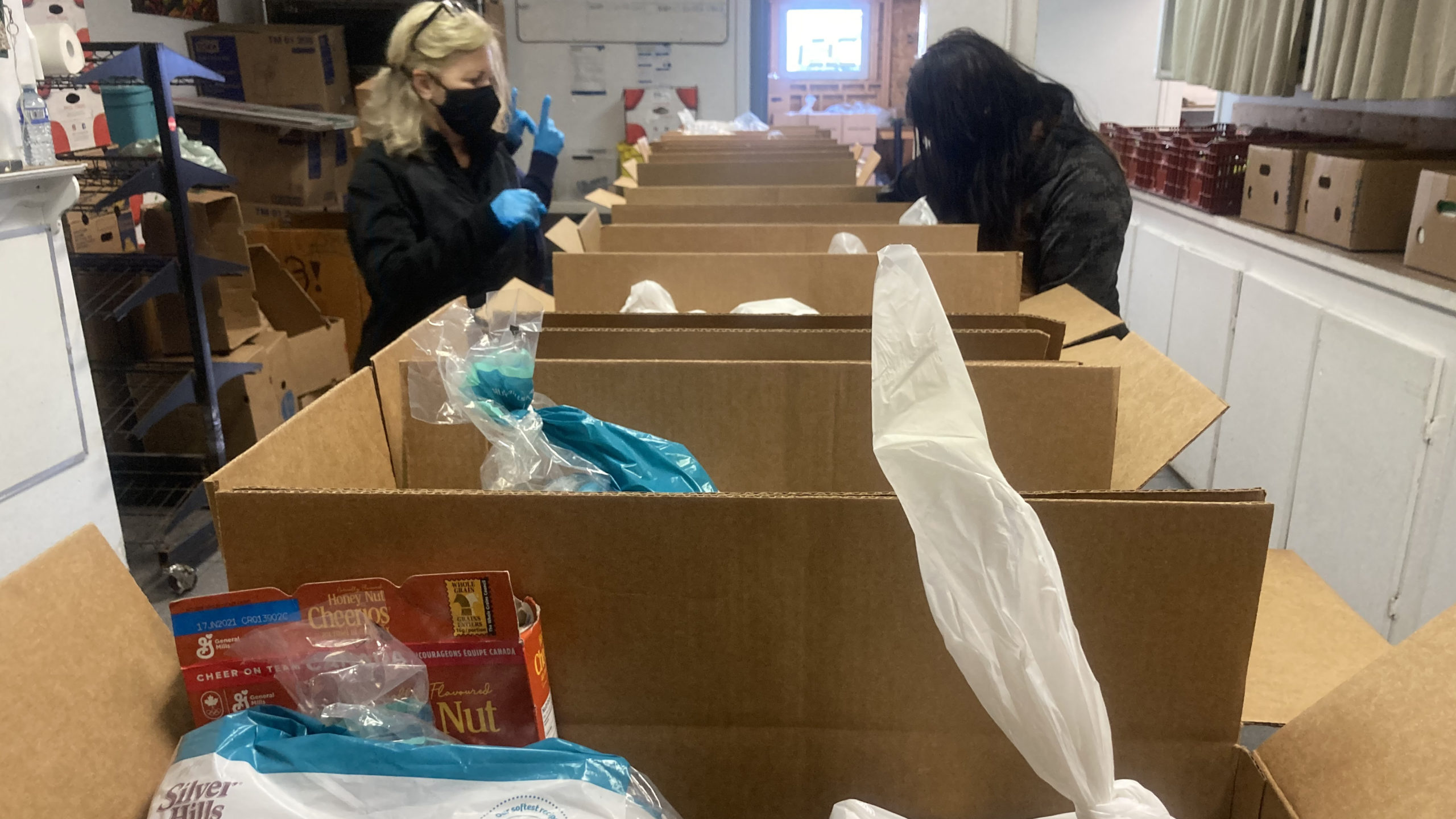 Volunteers pack food boxes at Parker Street Food and Furniture Bank.