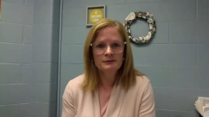 Deanna Rawding sits in a gray brick office.