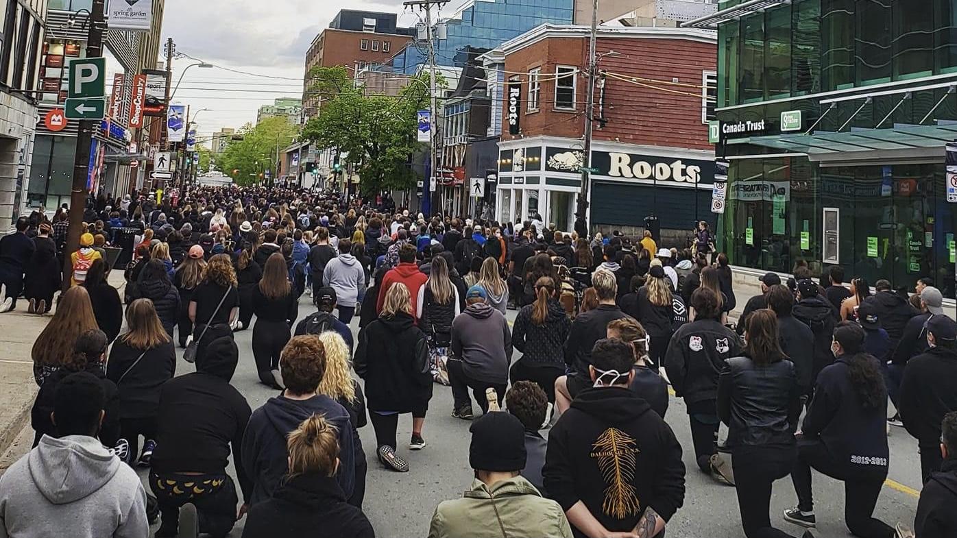 Demonstrators take a knee on Spring Garden Road in June 2020 .
