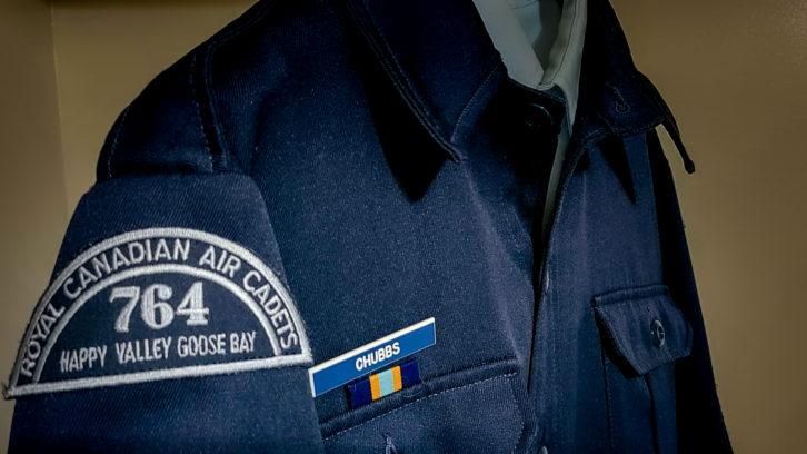An unused air cadet uniform hangs in a closet.