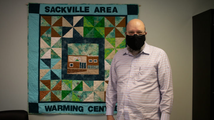 Mike Poworoznyk stands in front of a quilt inside the Sackville Area Warming Centre.