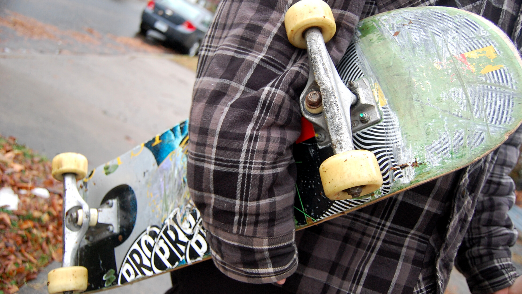 A person holding a skateboard under their arms.