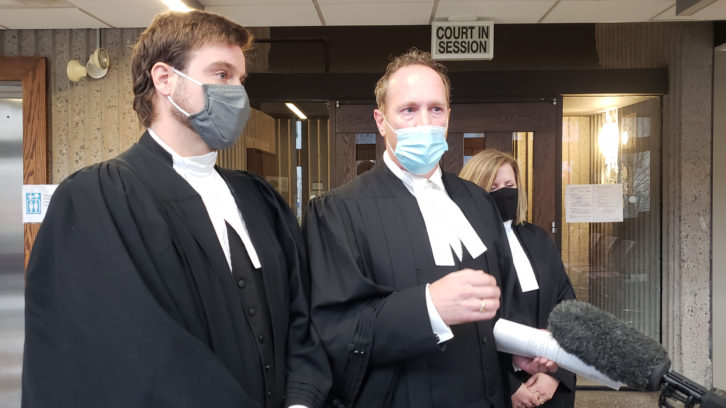 Senior Crown counsel Rick Woodburn (centre) comments on Justice Rosinski's decision Monday outside the courtroom.