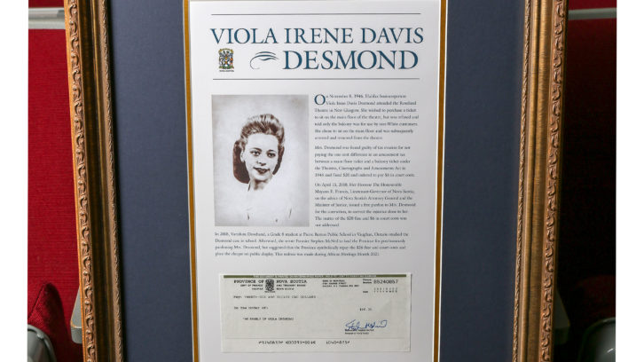 A framed copy of the official repayment cheque issued to the family of Viola Desmond is displayed alongside her pardon certificate.