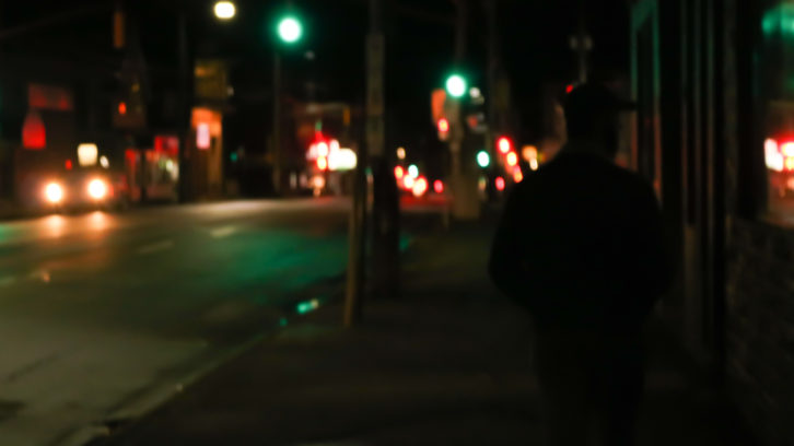 A landscape street view of Quinpool at night, with one car. Silhouette of a man on the right side of the image.