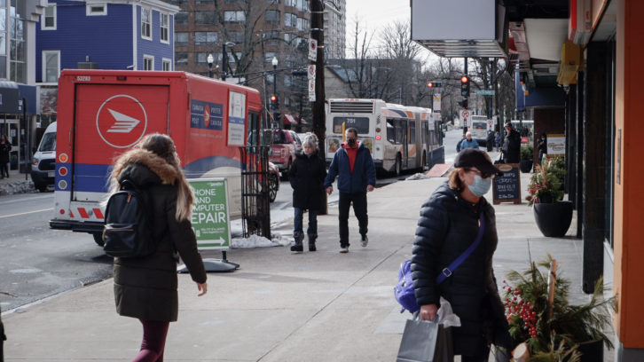 People walk down Spring Garden, one of Halifax's busiest streets. Businesses are operating on reduced capacity, and patrons must wear masks.