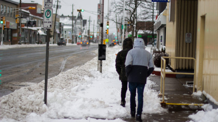 Pedestrians are walking on Quinpool Road in Halifax during Tuesday storm. Municipality recreation centers are closed.